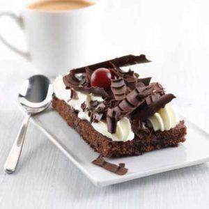 Pan di Spagna al cacao con crema gusto vaniglia decorato con fiocchi di cioccolato e ciliegia amarenata