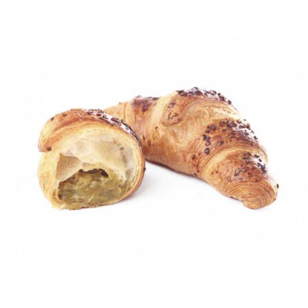 Delicato croissant farcito da punta a punta con crema al pistacchio e guarnito con granella di semi di zucca caramellati