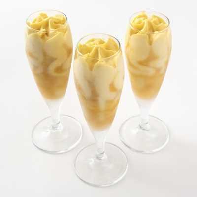 Gelato al mango con variegatura al frutto della passione. Servito in flute in vetro.